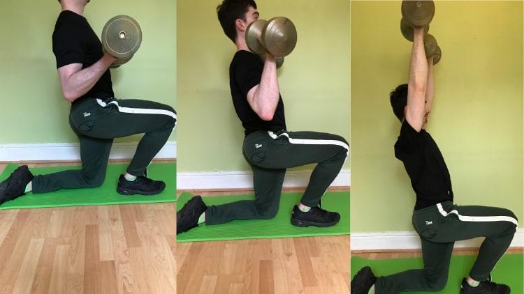 A man performing a half kneeling curl to press