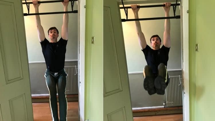 A man performing hanging leg raises