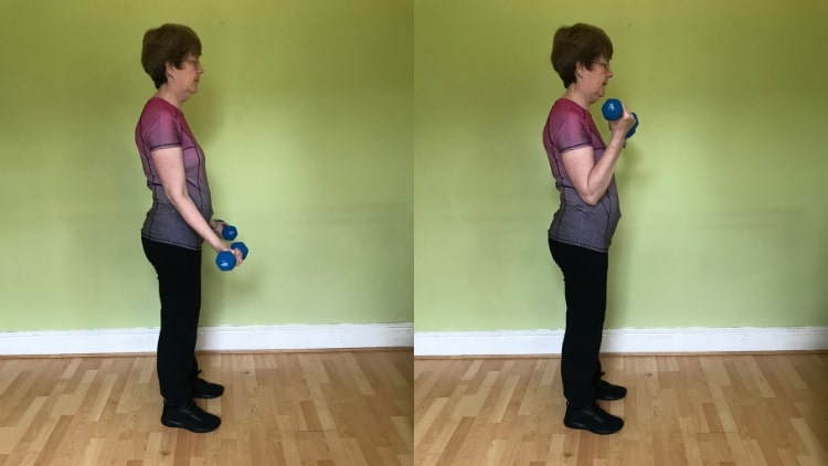 A lady doing dumbbell curls for her biceps