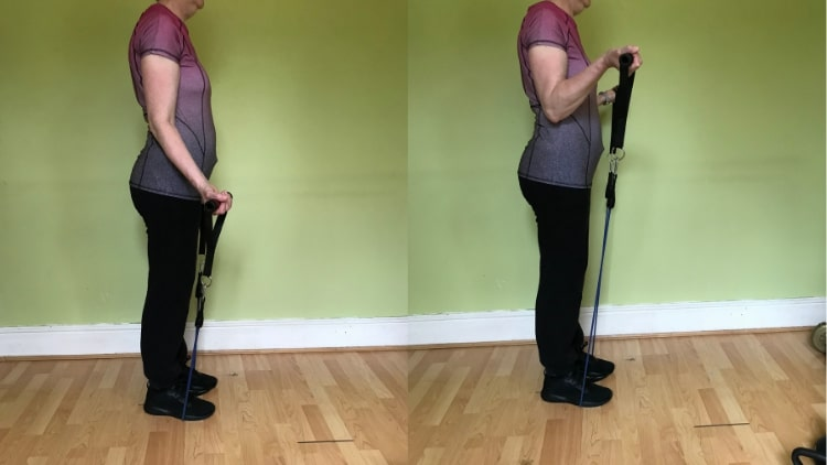 A lady doing resistance band curls for her biceps