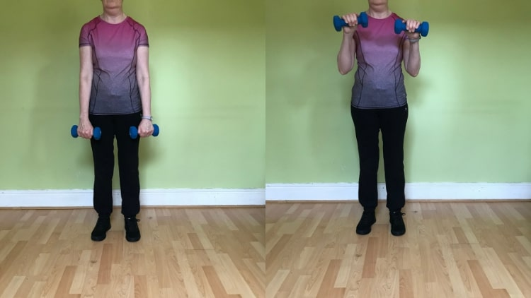 A lady demonstrating a reverse dumbbell curl