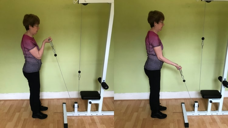 A woman doing a single arm cable curl