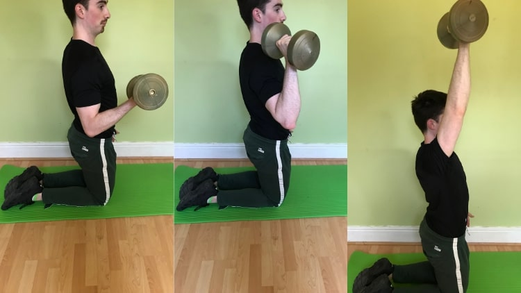 A man doing a single arm kneeling bicep curl to overhead press