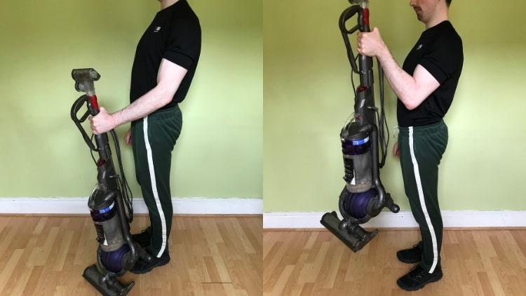 A man doing biceps curls with a vacuum cleaner
