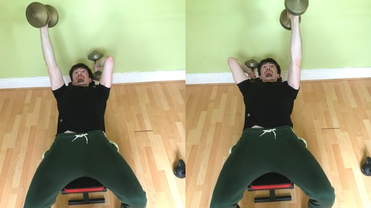 A man performing an alternating dumbbell lying triceps extension
