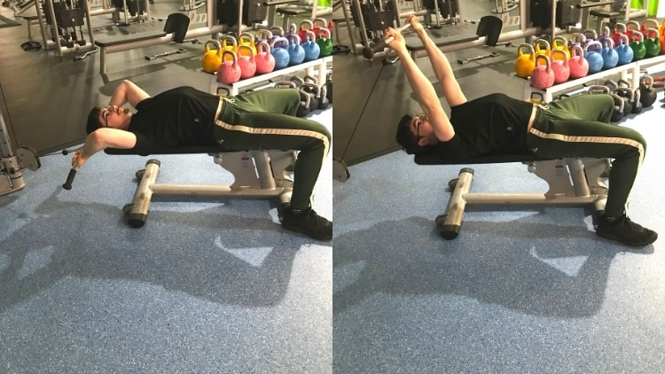 A man doing a cable lying tricep extension at the gym with a bar