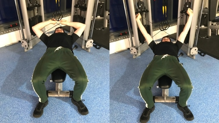 A man performing some cable lying tricep extensions at the gym