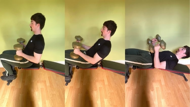 A man performing a decline lying triceps extension on a bench with dumbbells