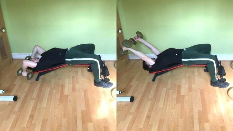A man performing dumbbell decline bench skull crushers