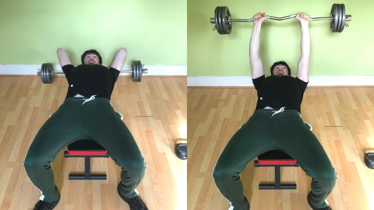 A man doing EZ bar lying triceps extensions during his workout