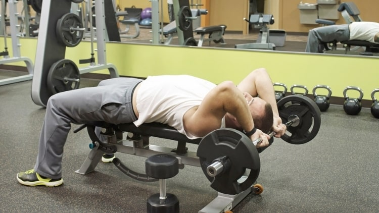 A man performing a flat bench triceps extension at the gym