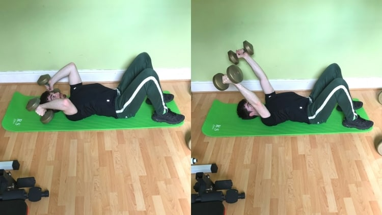 A man doing a floor dumbbell tricep extension on an exercise mat