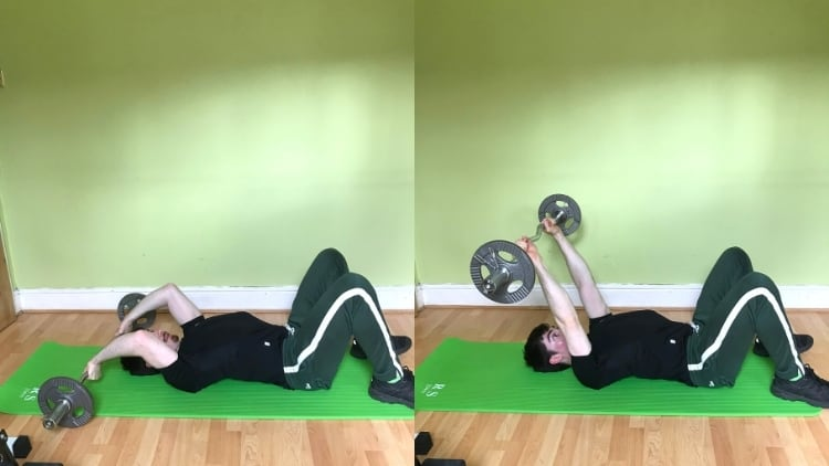 A man doing a floor tricep extension with a bar
