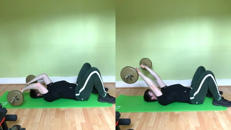 A man doing floor tricep extensions with a barbell
