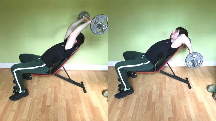 A man doing incline skull crushers on a bench to work his triceps