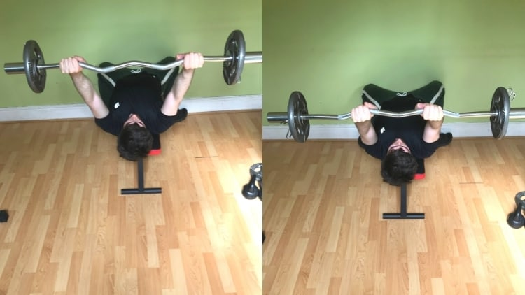A man doing lying cambered bar extensions for his triceps