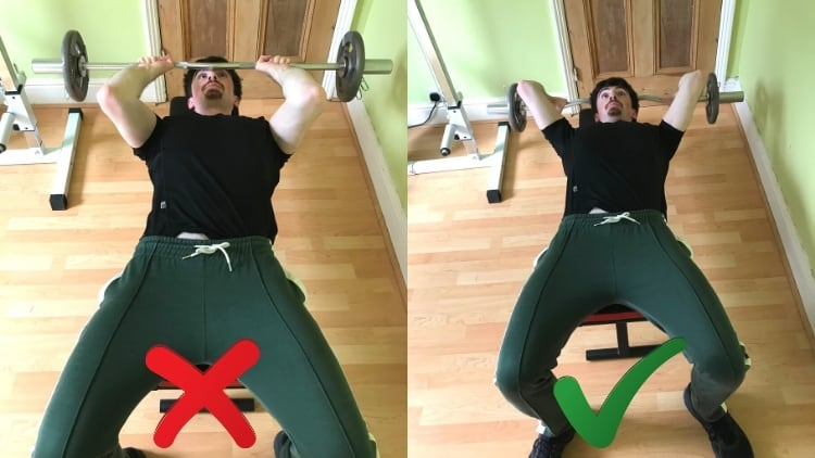 A man doing lying down triceps extensions during his workout