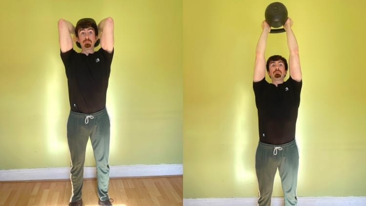 A man doing a standing overhead kettlebell tricep extension exercise