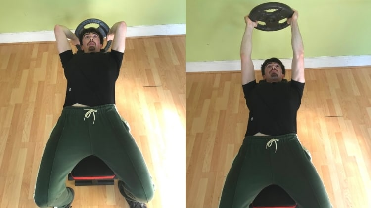 A man performing a plate skull crusher for his triceps