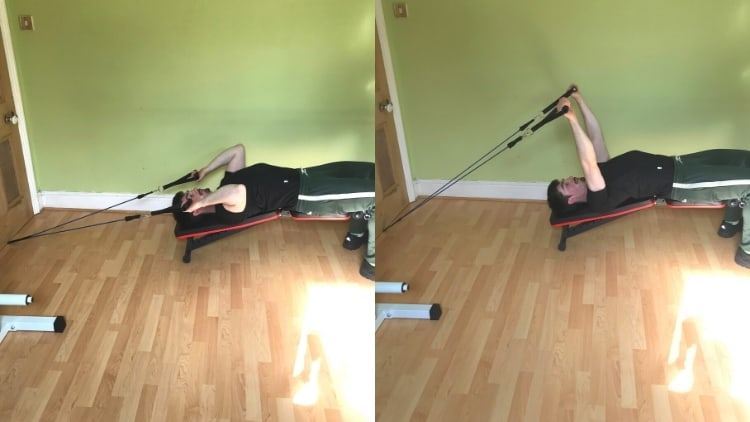 A man doing resistance band decline bench skull crushers