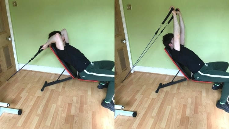 A man performing a resistance band incline skull crusher