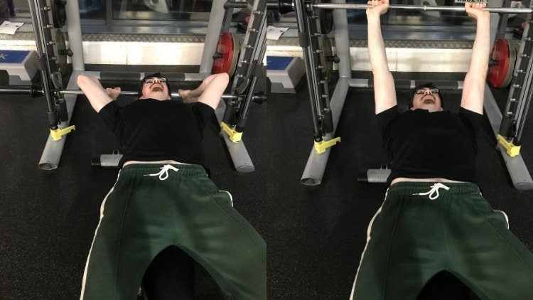 A man performing a skull crushers on a Smith machine