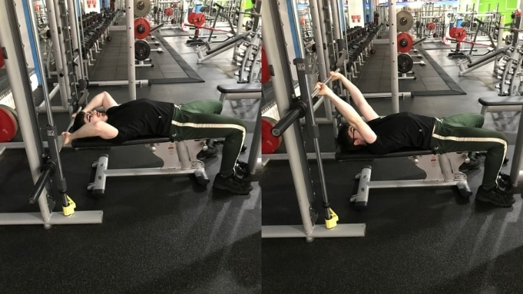 A man doing Smith machine skull crushers for his triceps