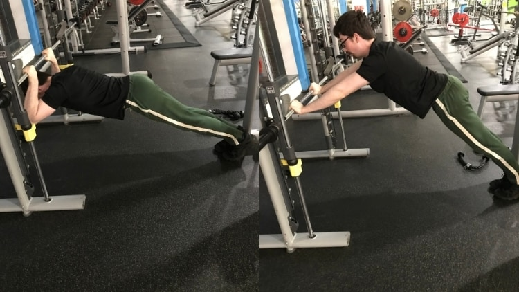 A man performing standing Smith machine skull crushers at the gym