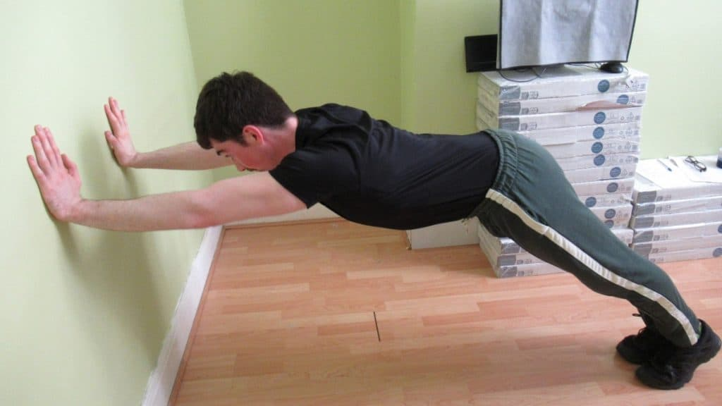 A man performing against the wall tricep extensions