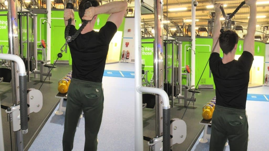 A man at the gym doing cable overhead extensions to train his triceps