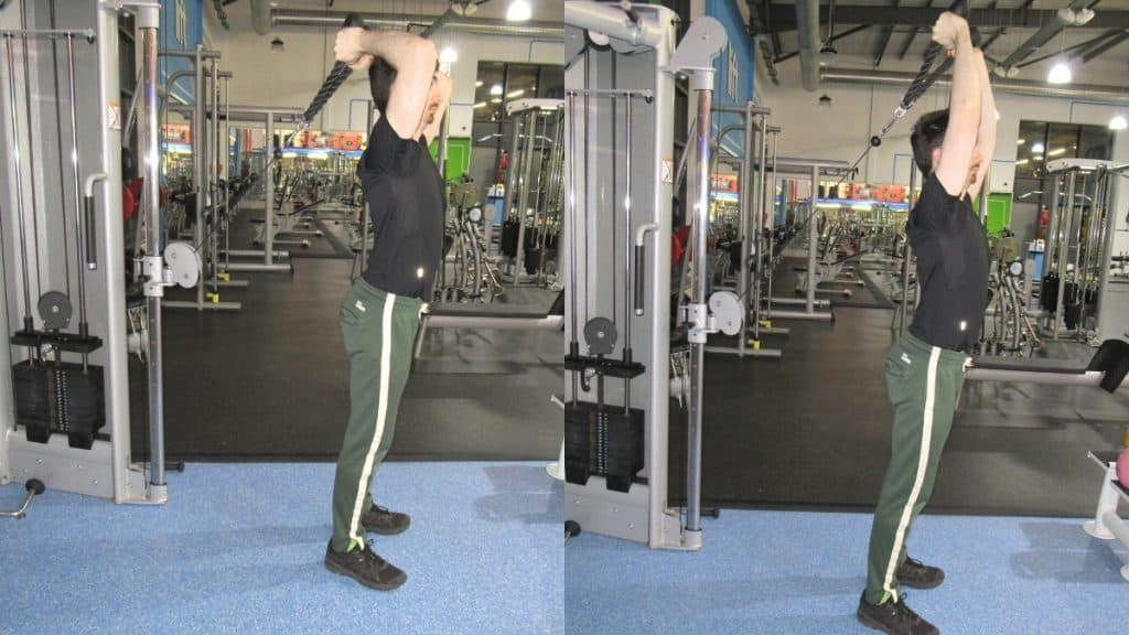 A man at the gym doing a cable overhead rope extension to work his triceps