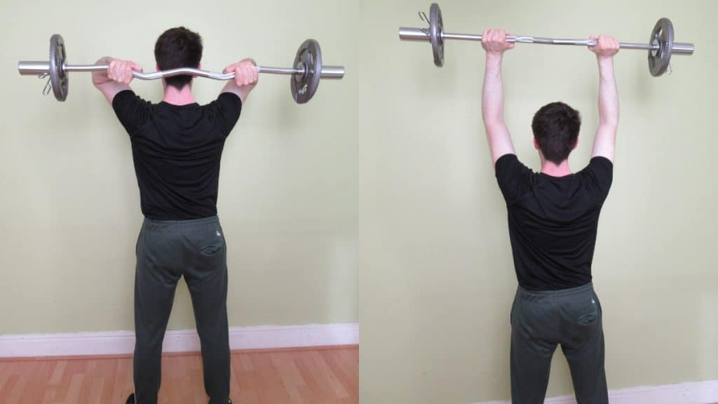 A man doing a cambered bar overhead tricep extension