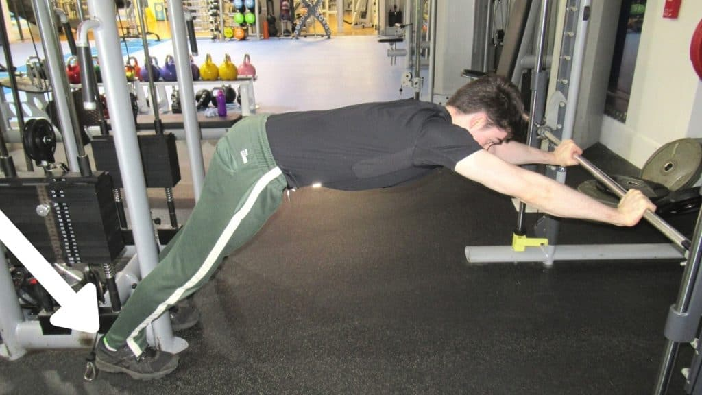 A man doing a fixed bar triceps extension at the gym