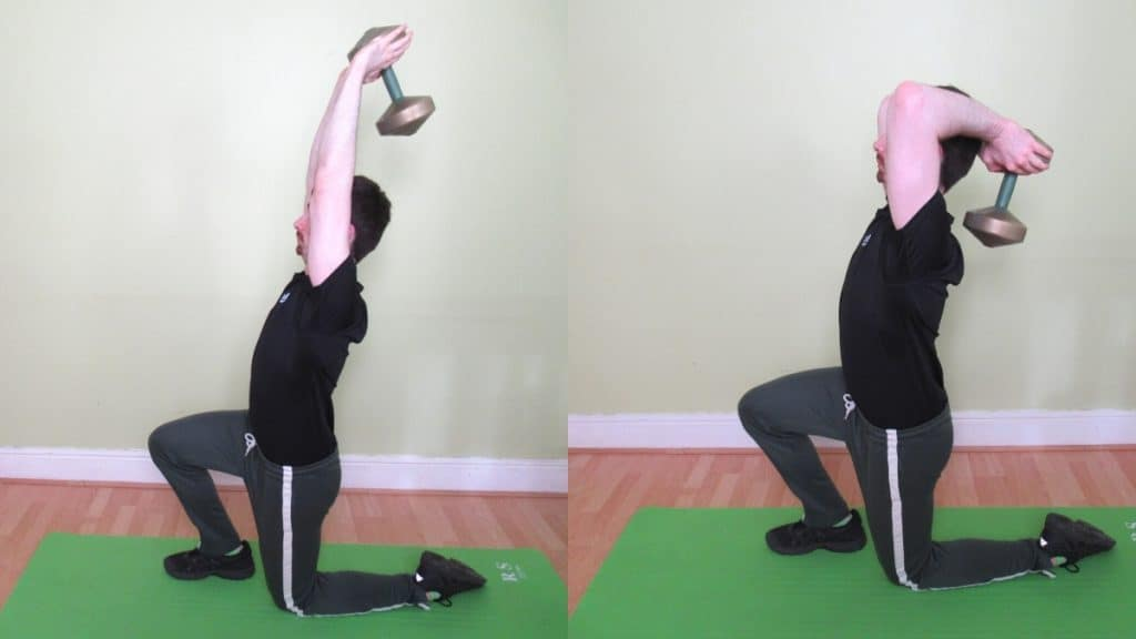A man performing a half kneeling overhead extension with a dumbbell