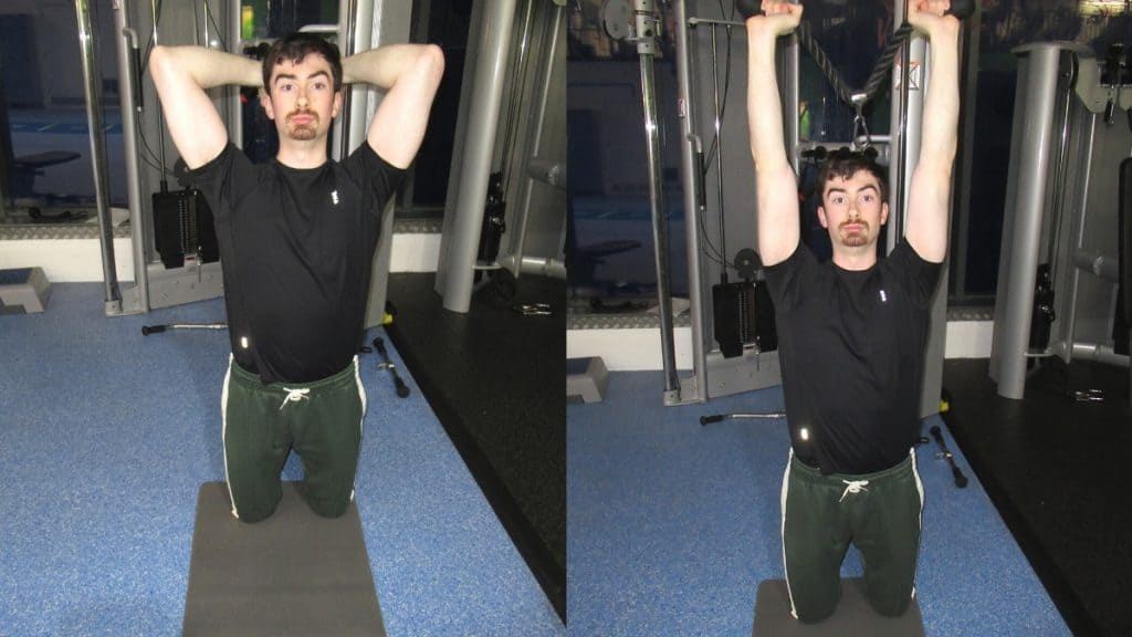 A man performing a kneeling overhead cable tricep extension at the gym