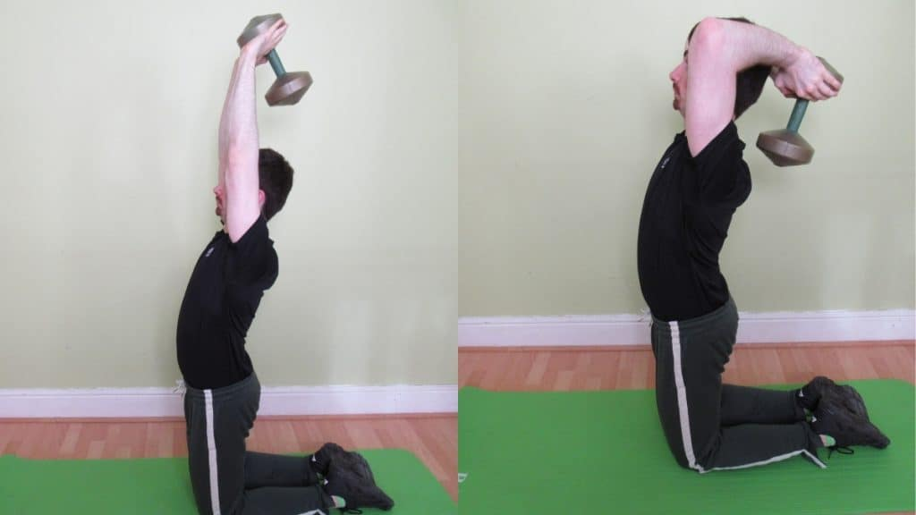 A man doing an overhead kneeling tricep extension with a dumbbell