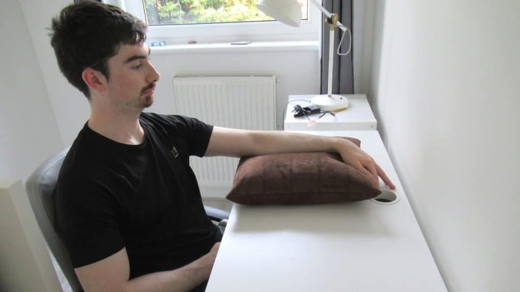 A man resting his elbow on a cushion