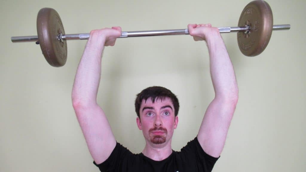 A man doing overhead bar extensions for his triceps