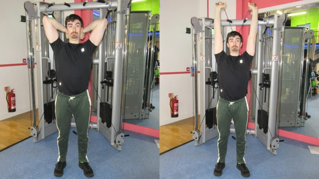 A man performing overhead cable extensions for his triceps at the gym
