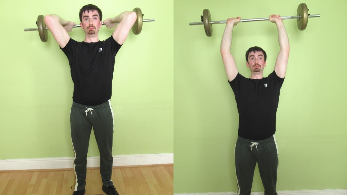 A man performing an overhead standing barbell tricep extension during his workout