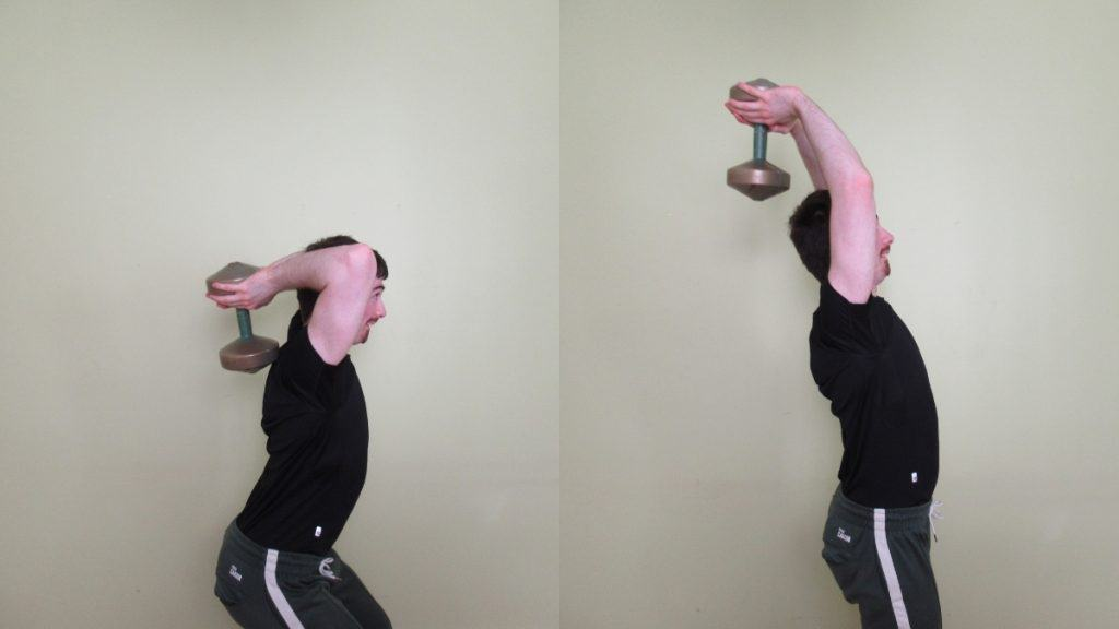 A man using momentum to lift the dumbbell during an overhead standing tricep extension