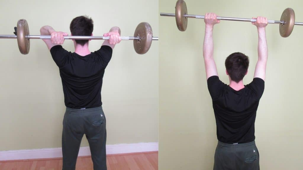 A man doing a standing overhead tricep extension with a barbell