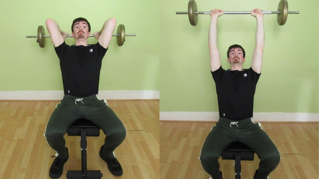 A man performing a seated barbell extension for his triceps