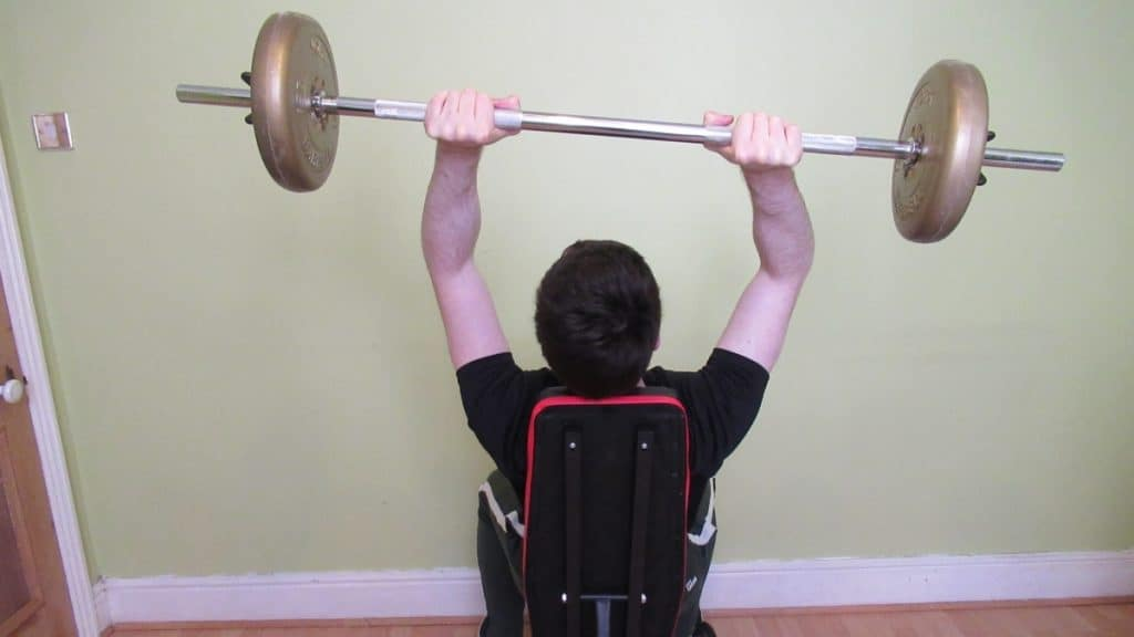 A man making a common seated BB extension mistake: letting the bar become lopsided