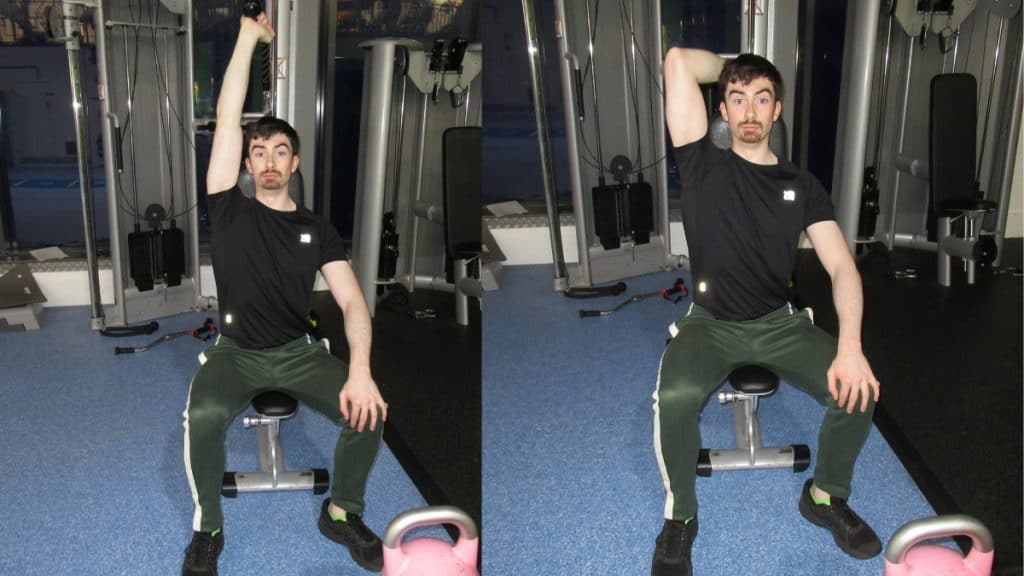 A man doing a seated one arm overhead cable triceps extension