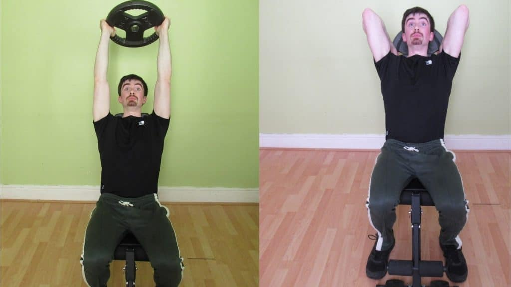 A man performing a seated overhead plate triceps extension