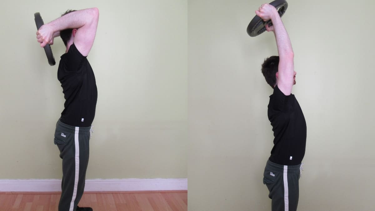 A man doing a standing overhead plate tricep extension