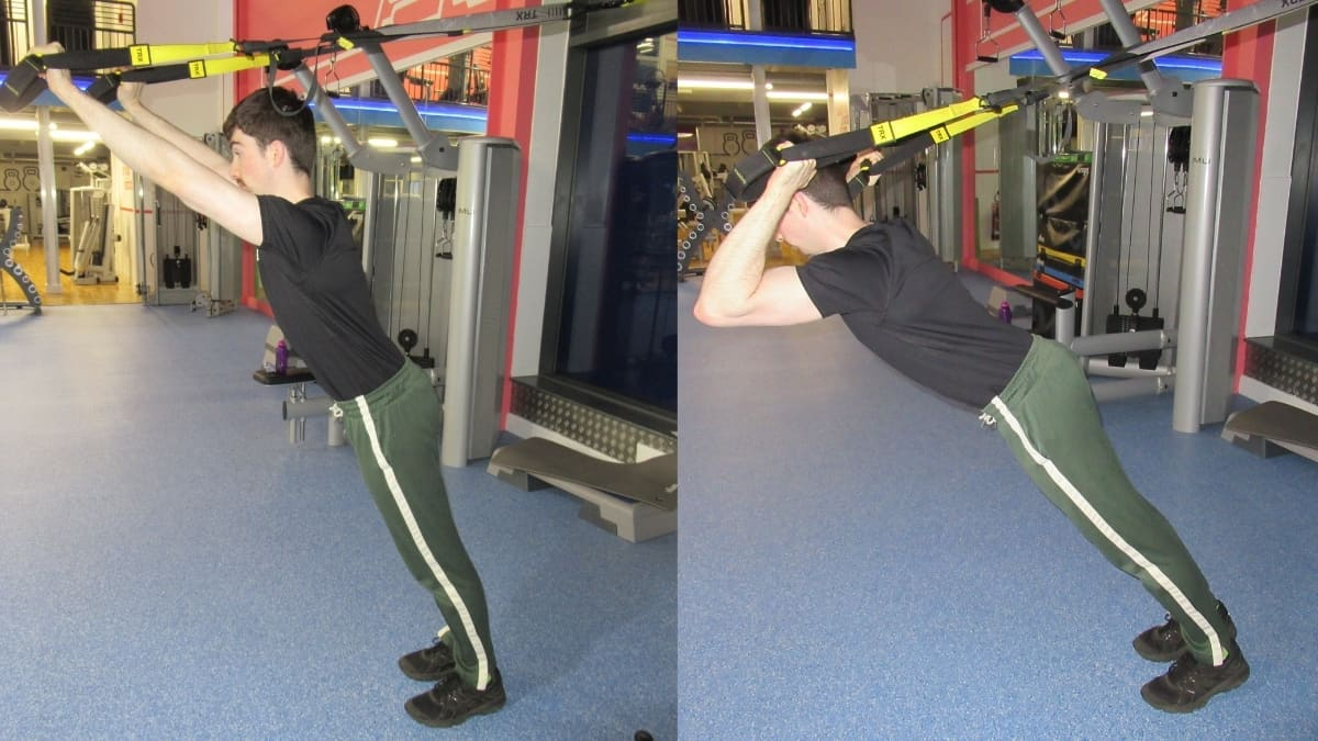 A man doing a tricep extension with a TRX suspension trainer