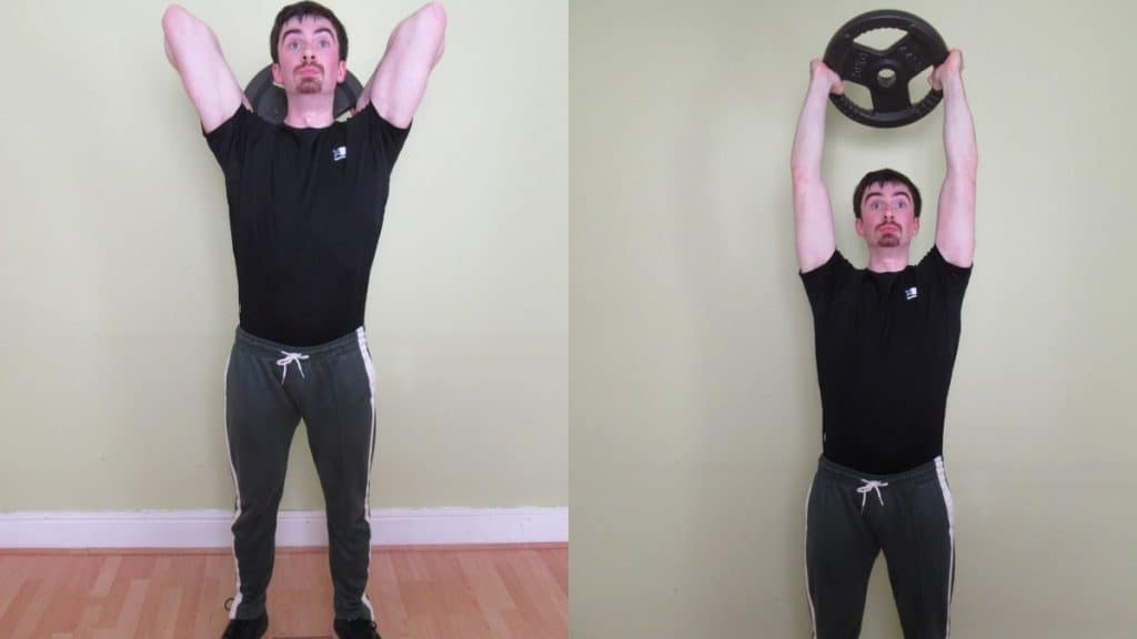A man performing a tricep extension with a weight plate