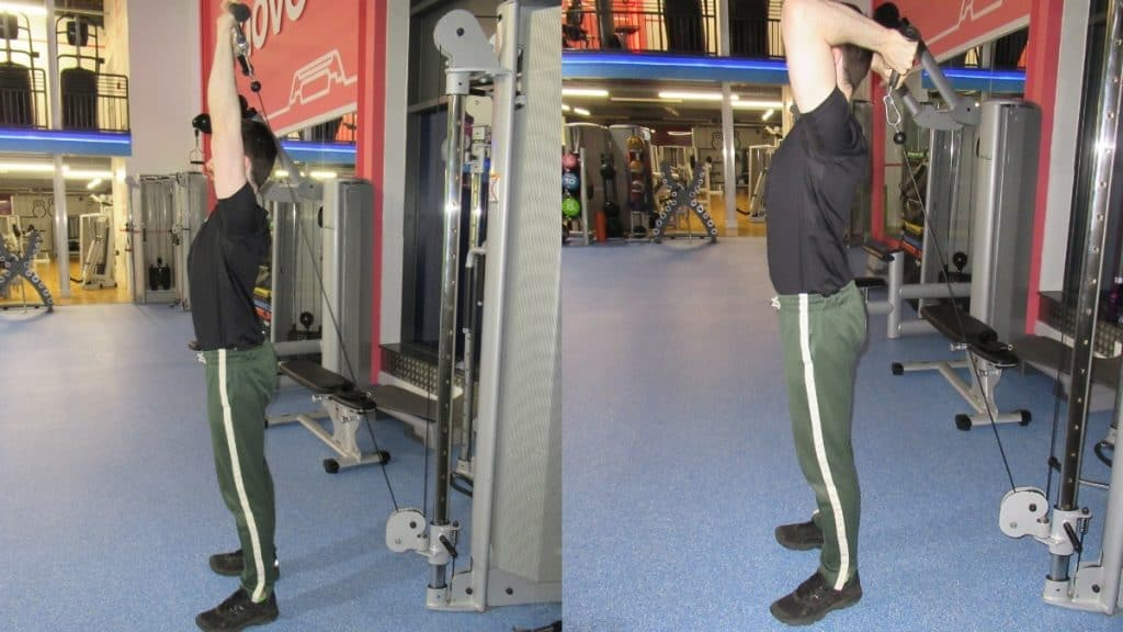 A man at the gym doing a v bar overhead tricep extension